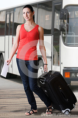 Summer woman with suitcase and travel ticket walking at the bus station