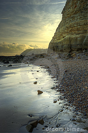 Beautiful sunrise landscape over beach with cliff