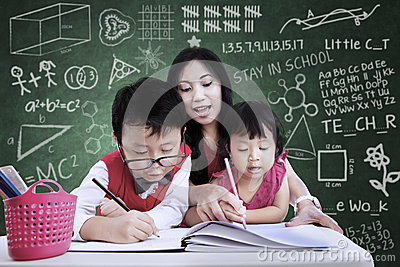 Beautiful teacher help children to write in class