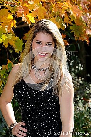 Beautiful teen country girl among fall foliage