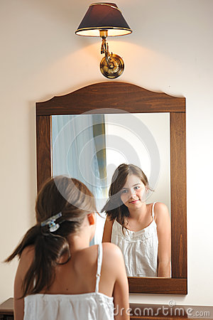A beautiful teen girl studies her appearance as she looks into the mirror