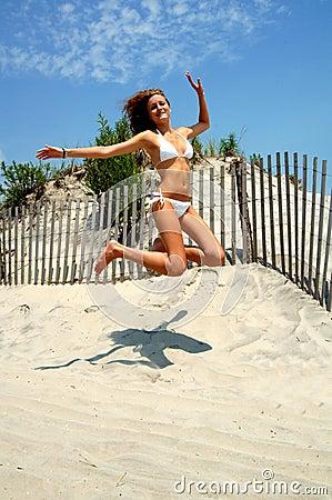 Beautiful teen jumping at beach