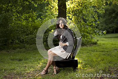 Beautiful teen sitting on a bench in park