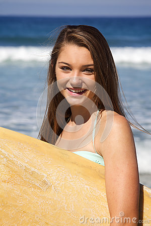 Free Beautiful Teenage Girl Holding A Surfboard At The Beach Smiling Stock Photo - 78838730