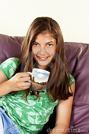 Beautiful teenage girl with hot drink at home