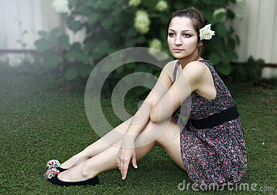 Beautiful teenage girl sitting on grass