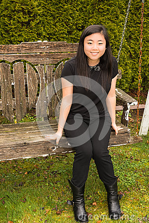 Beautiful Teenage Girl Sitting on Wooden Swing