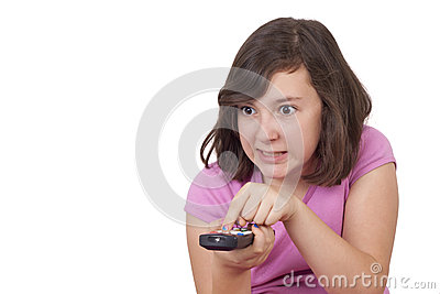 Beautiful teenage girl with tv remote control in her hands