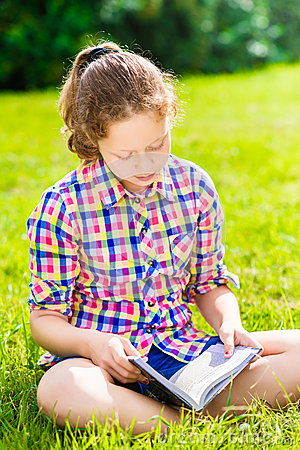 Beautiful teenager girl sitting on the grass and reading book