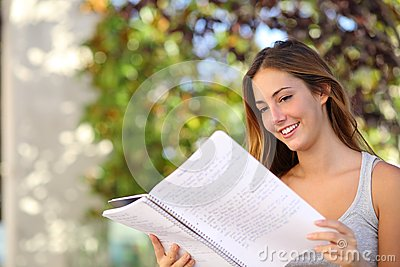 Beautiful teenager girl studying reading a notebook outdoor