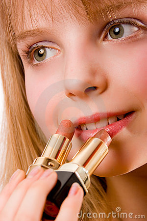 Beautiful teenager girl with two lipsticks in hand
