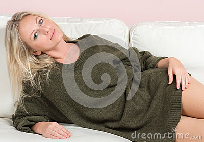 Beautiful tender woman in sweater on a sofa