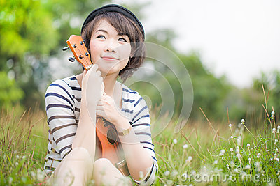 Beautiful thai woman with Ukulele in garden