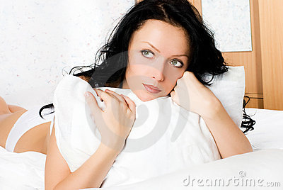 Beautiful thoughtful woman on the bed