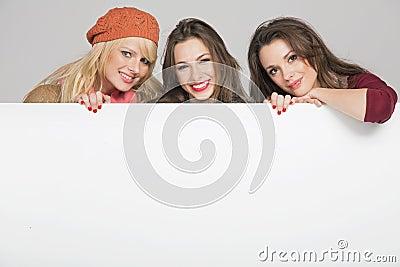 Beautiful three female friends with empty board