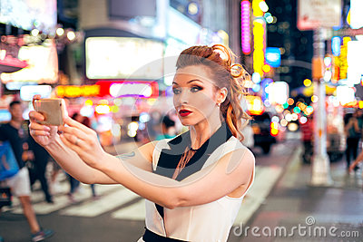 Beautiful tourist woman fashion blogger taking photo selfie on night Time Square in New York City
