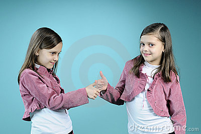 beautiful twin sisters showing ok sign