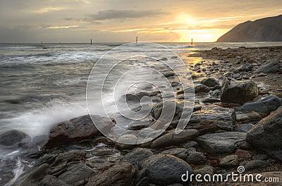 Beautiful vibrant sunrise over ocean with rocks