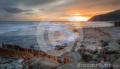 Beautiful vibrant sunrise over rocky beach