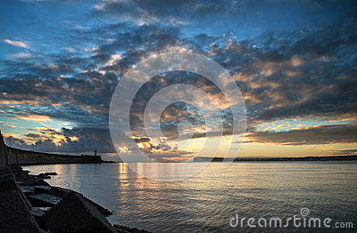 Beautiful vibrant sunrise sky over calm water ocean with lightho
