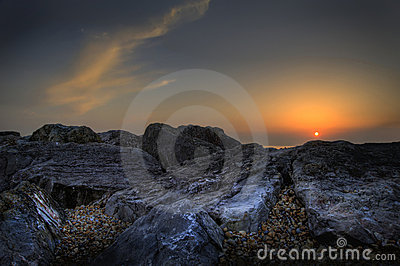 Beautiful vibrant sunset over beach with rocks