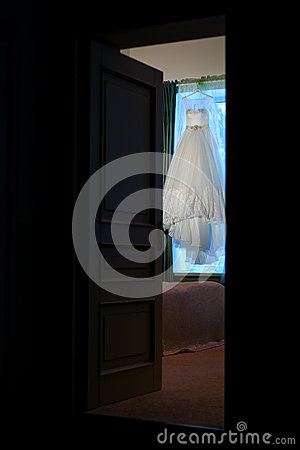 Free Beautiful Wedding Dress Hanging In The Doorway Stock Photography - 65070872