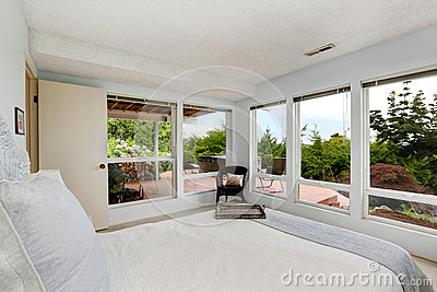 Beautiful white bedroom with glass wall