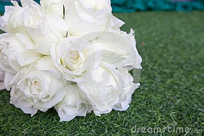 Beautiful white wedding flowers bouquet on the green grass