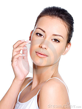 Beautiful woman applying cosmetic cream on face