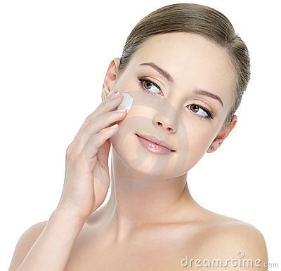 Beautiful woman applying cream on face