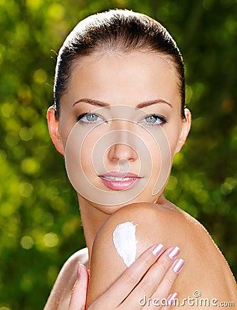 Beautiful woman applying cream on shoulder