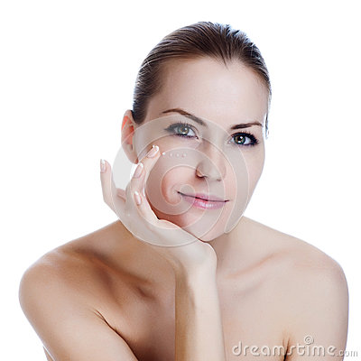 Beautiful woman applying cream on skin near eyes