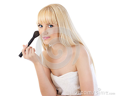 Beautiful woman applying makeup with brush