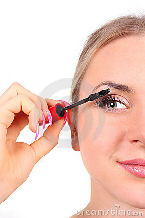 Beautiful woman applying mascara on her eyelashes