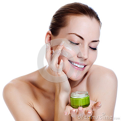 Beautiful woman applying moisturizer cream