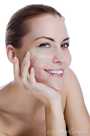 Beautiful woman applying moisturizer cream