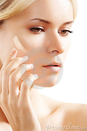 Beautiful woman applying skin tone cream on cheek