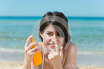 Beautiful woman applying sunscreen to her nose