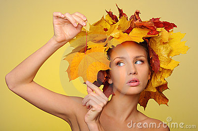 Beautiful woman with autumn leaves on yellow