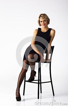 Beautiful woman in black dress posing sitting on a chair