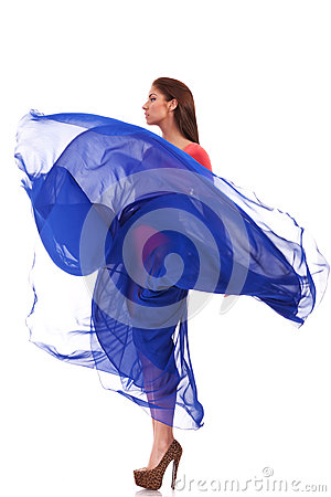 Beautiful woman in blue waving flying dress