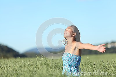 Beautiful woman breathing happy with raised arms in a green oat meadow