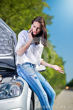 Beautiful woman with car trouble talking over phone