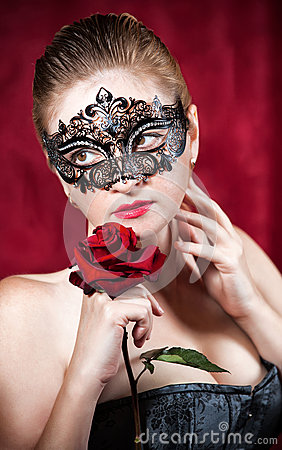 Beautiful woman in carnival mask with red rose