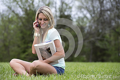 Beautiful woman on cellphone holding books