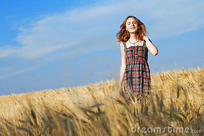 Beautiful woman in checkered dress in a field