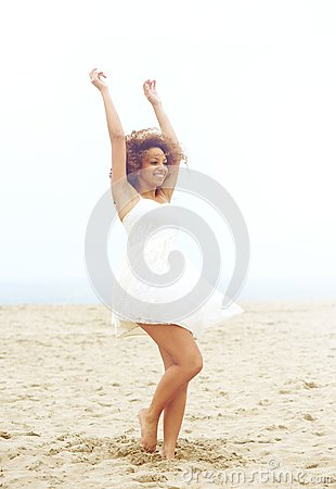 Beautiful woman with cheerful expression dancing at the beach in white dress