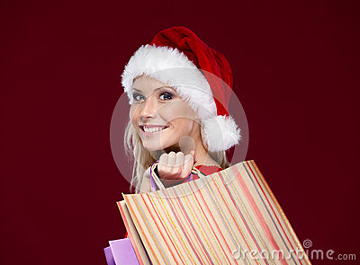 Beautiful woman in Christmas cap hands packets