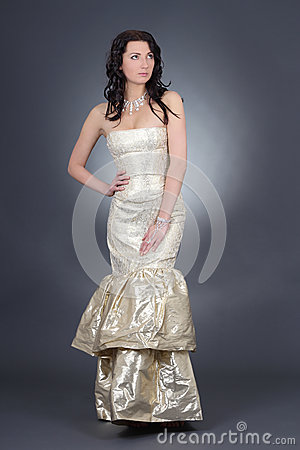 Beautiful woman with curly hair in golden dress