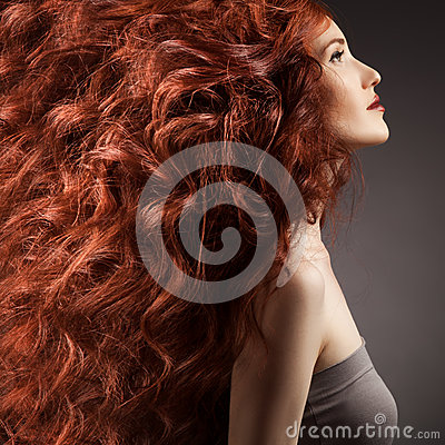 Beautiful woman with curly hair on gray background